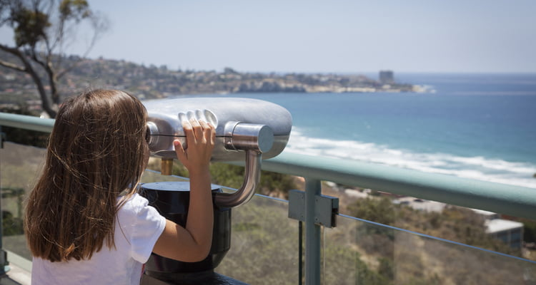 san diego kid looking over water san diego charter bus company