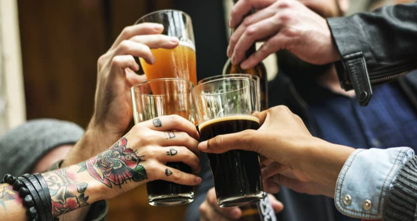 Closeup of people's hands toasting a beer