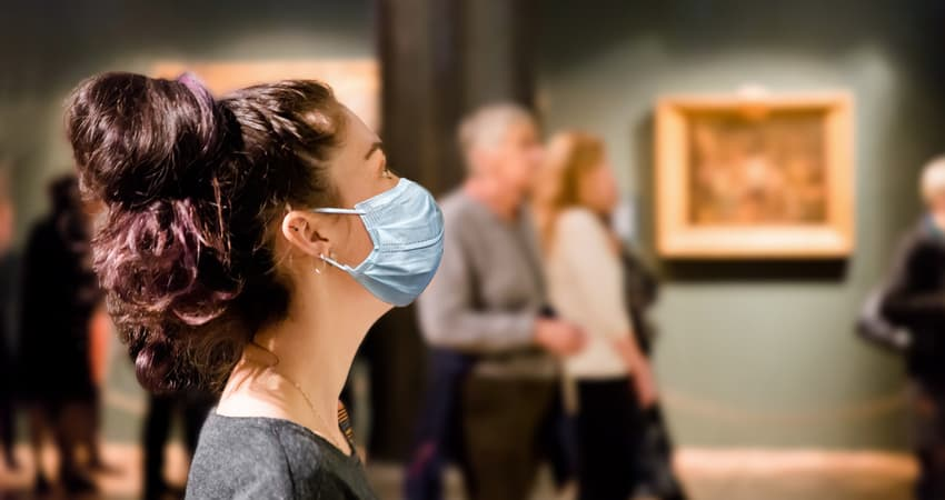 A patron wearing a mask while viewing work in a museum gallery