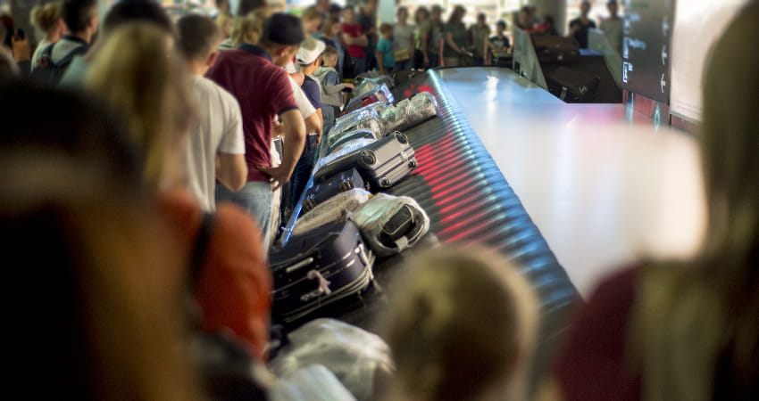 A crowd of people look for luggage at an airport baggage claim