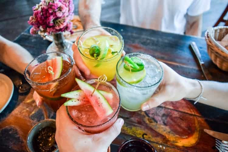 Four people drinking cocktails