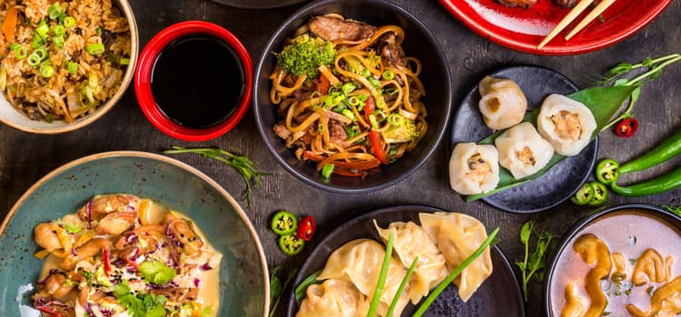 a table filled with dumplings, noodles, sauces, and vegetables