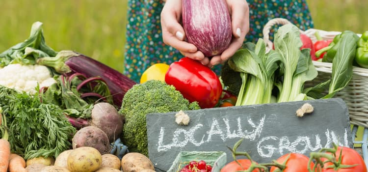 """someone holds a vegetable over a table of vegetables with a sign that reads """"locally grown"""""""