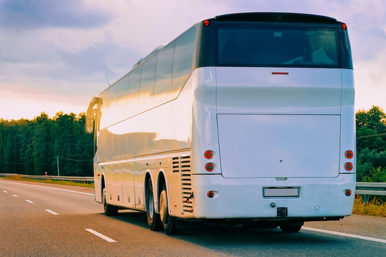 Charter bus driving down road at sunset