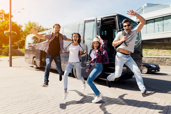 a group of travelrs jump in celebration as they exit their San Diego charter bus